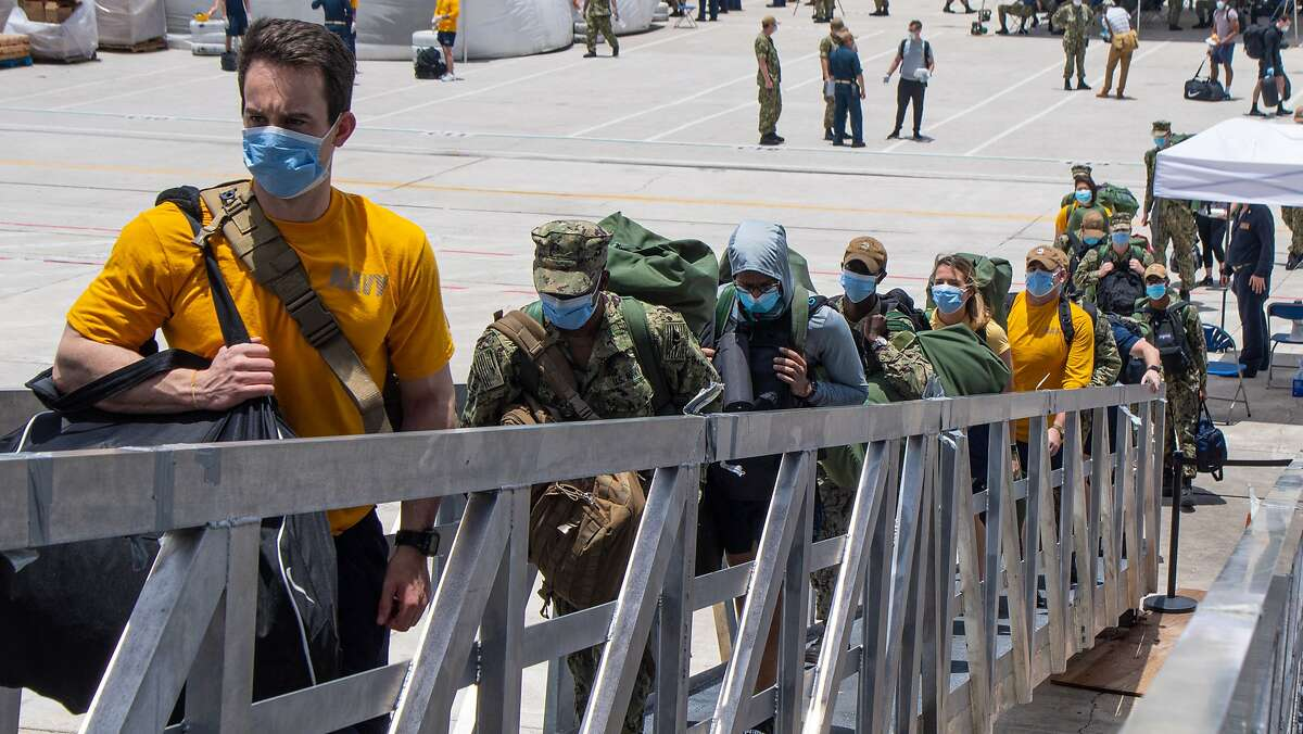 Sailors assigned to the aircraft carrier USS Theodore Roosevelt board the ship, May 2, 2020.