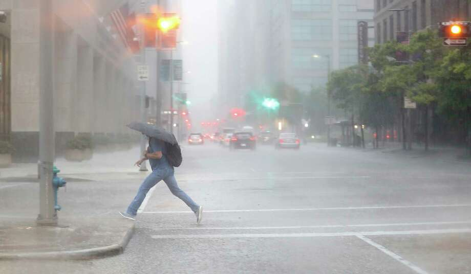 A man leaps onto a sidewalk holding an umbrella downtown in Houston, Friday, May 15, 2020. Photo: Karen Warren, Staff Photographer / © 2020 Houston Chronicle