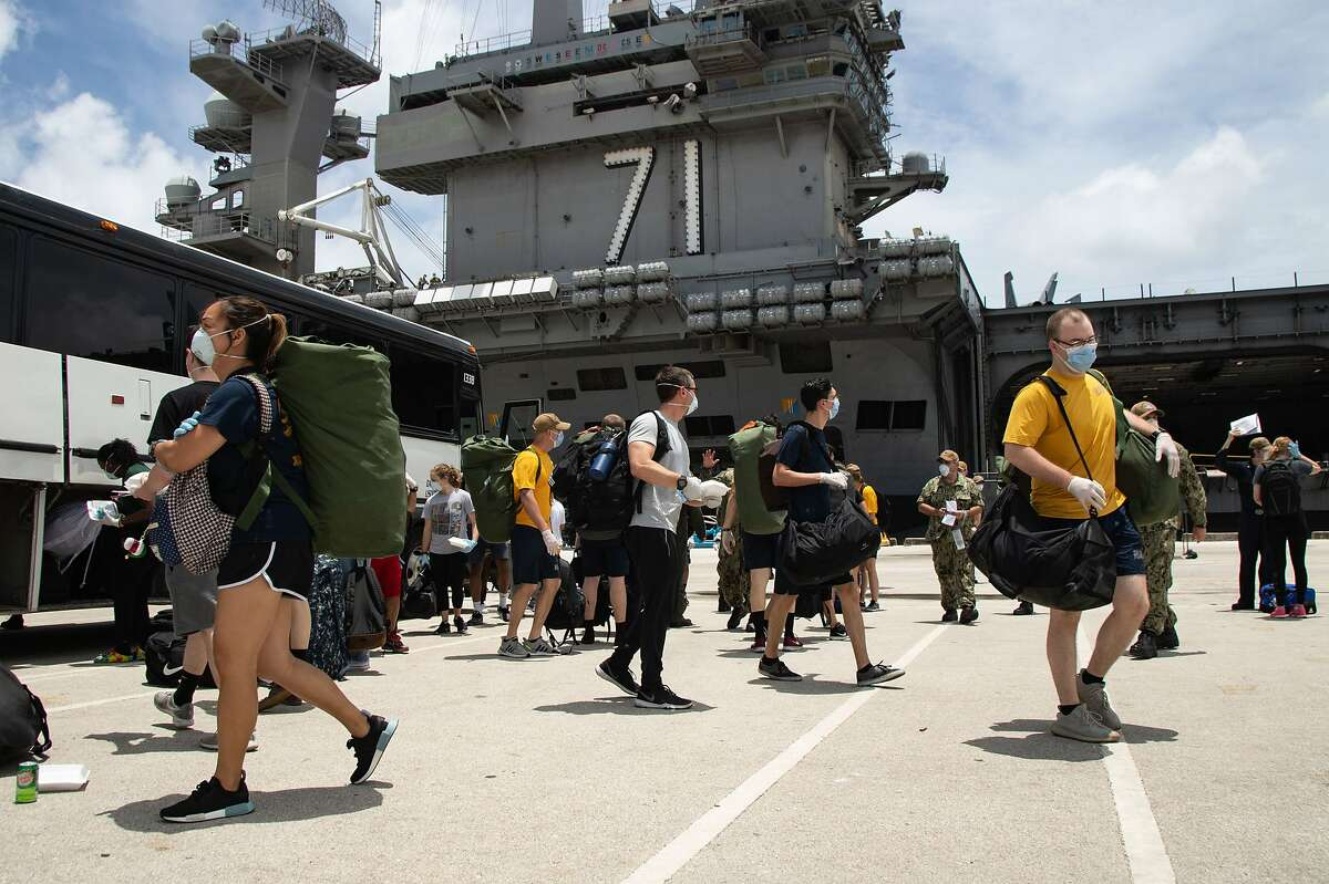 200502-N-KB540-3012 NAVAL BASE GUAM (MAY 2, 2020) Sailors assigned to the aircraft carrier USS Theodore Roosevelt (CVN 71) return to the ship, May 2, 2020. Theodore Roosevelt's essential watch standers and cleaning team conducted a crew swap starting April 29, turning over a clean ship to a COVID-negative crew after completion of their off-ship quarantine or isolation. (U.S. Navy photo by Mass Communication Specialist Seaman Alexander Williams/Released)