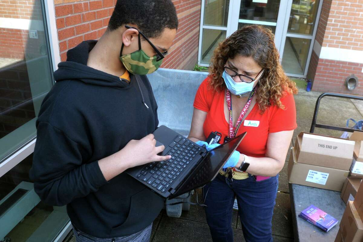 Teacher Ana Batista helps eight grader Jelson Martinez with a new Chromebook computer during the weekly free meal giveaway at Cesar Batalla School, in Bridgeport, Conn. May 15, 2020.  3.