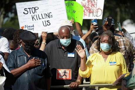 People pray during a rally Friday, May 8, 2020 to protest the shooting of Ahmaud Arbery, in Brunswick Ga. Two men have been charged in the February shooting death of Arbery after they saw him running in their neighborhood.