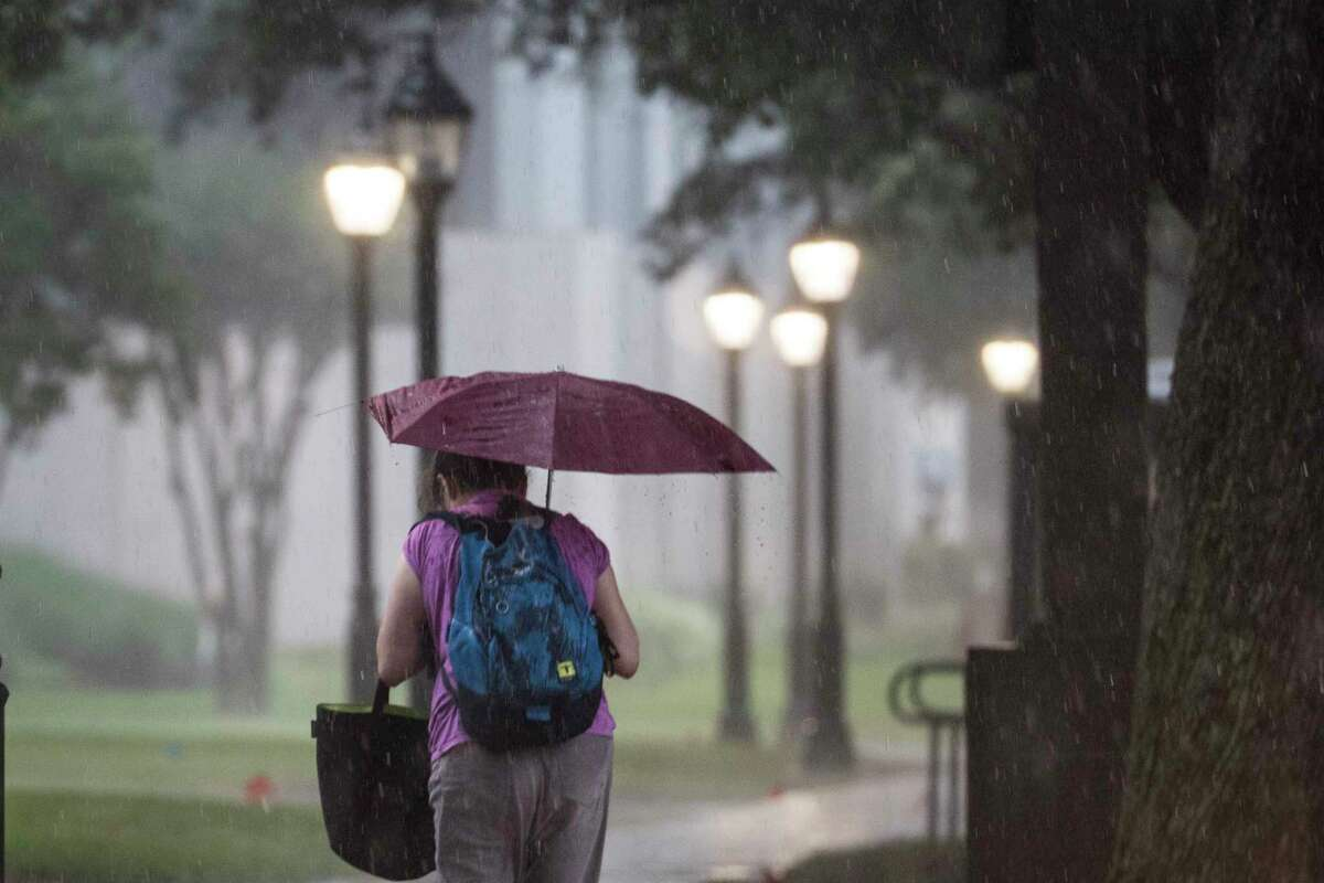Heavy rain comes down on pedestrians in the Texas Medical Center on Friday, May 15, 2020 in Houston. Thunderstorms are forecast through Saturday.