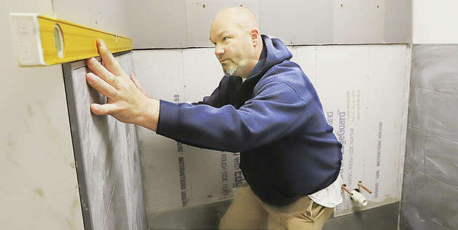 Michael Bold, with Facilities Management for Madison County, checks the level of tiles being installed on a first floor ladies restroom inside the Madison County Courthouse in Edwardsville Friday. The restroom is being completely re-done. The down time in courthouse activities is allowing facilities management to catch up on several maintenance projects.