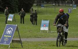 San Francisco Park Rangers guard an entrance that leads to Hippie Hill due to COVID-19 concerns on Monday, April 20, 2020, at Golden Gate Park in San Francisco. People annually gather on April 20, 4/20, to smoke marijuana on Hippie Hill. (AP Photo/Ben Margot)