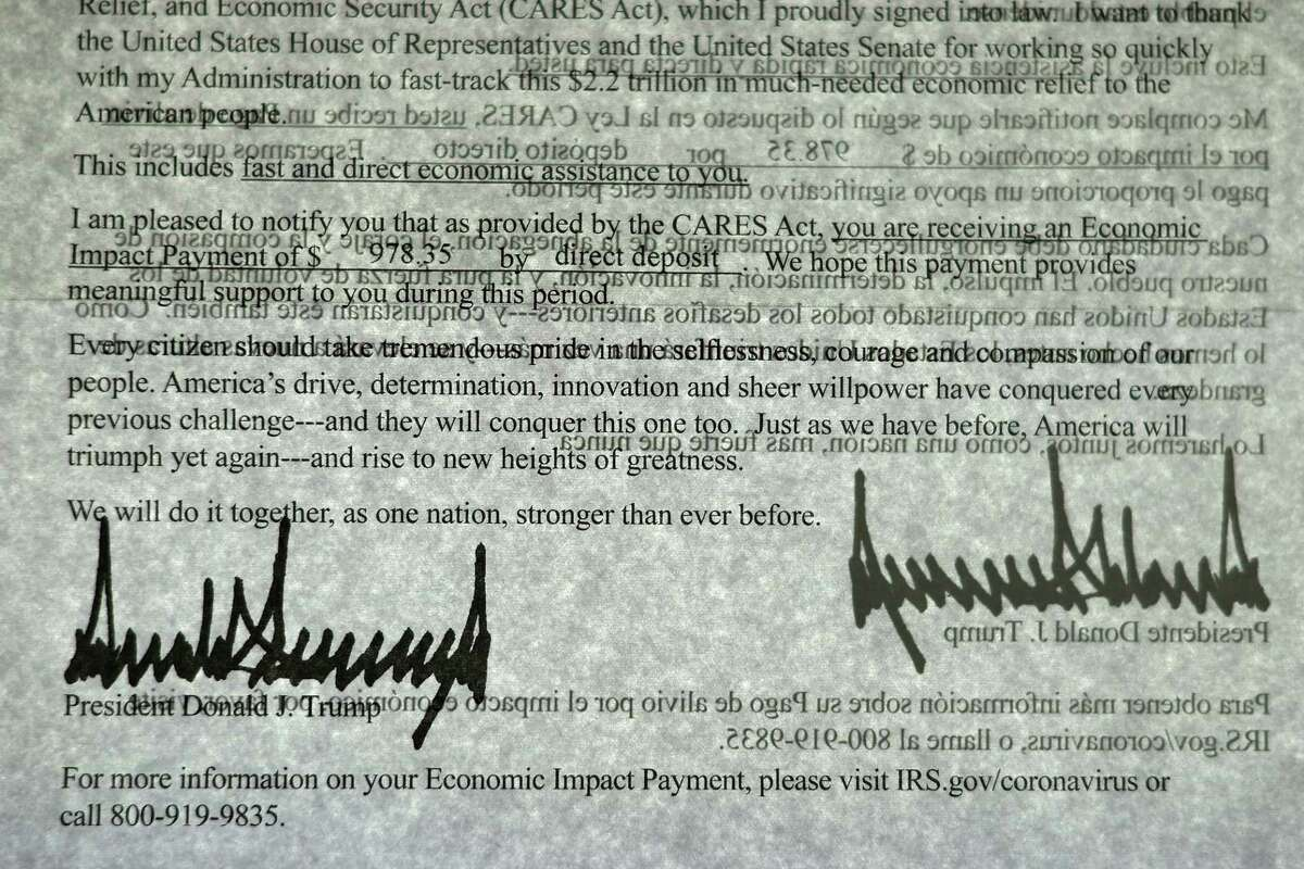 President Donald Trump's signature can be seen twice as light shines through a letter printed in both English and Spanish that was sent to people who received a coronavirus economic stimulus payment as part of the Cares Act April 29, 2020,in Washington, DC. The letter had a return address for the Internal Revenue Service in Austin, Texas, but was printed on White House letterhead. The initial 88 million payments totaling nearly $158 billion were sent by the Treasury Department as most of the country remained under stay-at-home orders due to the COVID-19 pandemic.