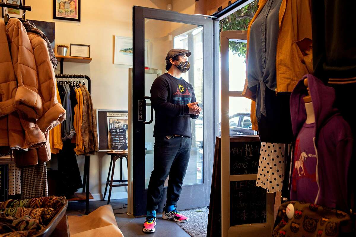 Asmbly Hall owner Ron Benitez looks out the door of his store after removing a panel of brown paper during re-opening preparations in San Francisco, Calif. Friday, May 15, 2020. Benitez lost 90% of his revenue during the shut down of non-essential business and was forced to lay off both his employees. He plans to hold a limited re-opening on Monday, May 19 with a merchandise table placed outside the front doors and pick-up orders only.