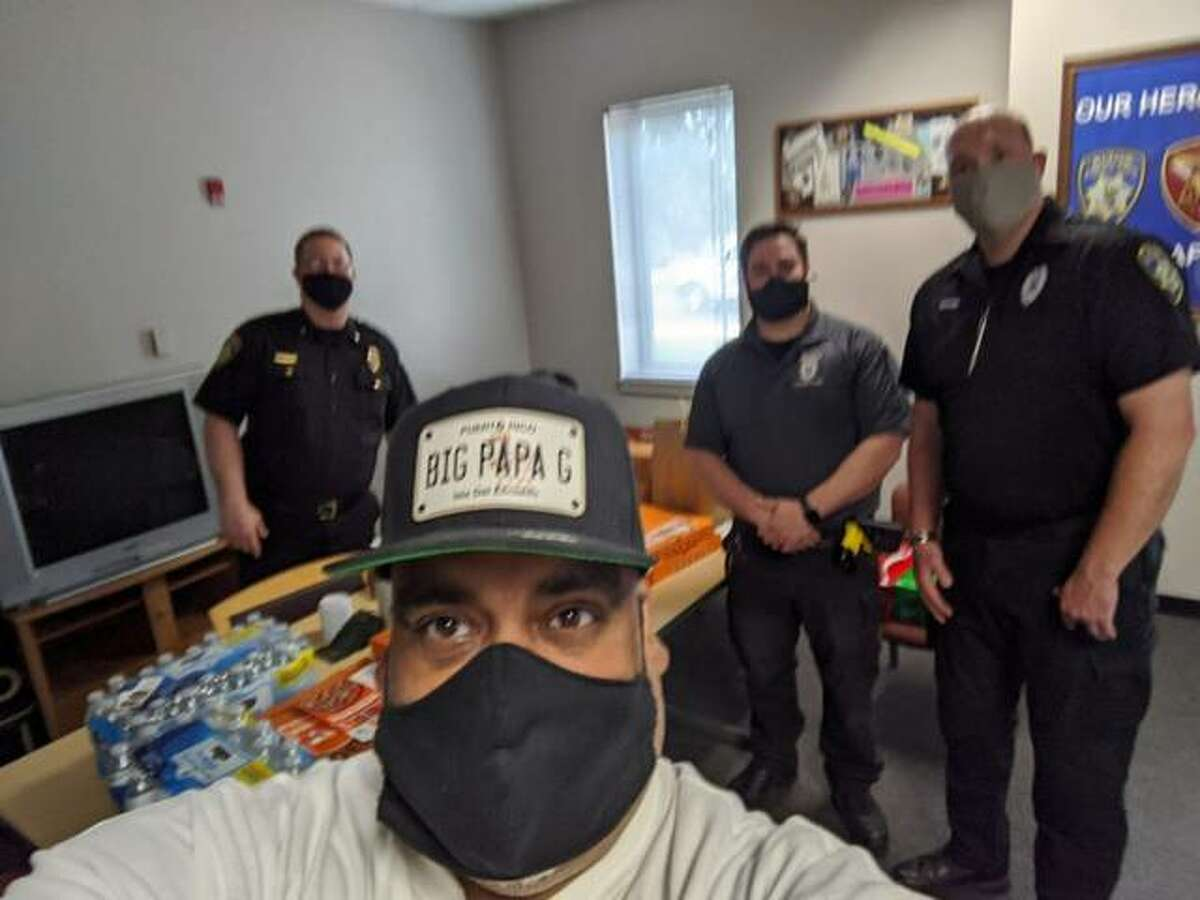 """Greg Horta, also known as """"Big Papa G,"""" is pictured with members of the Alton Police Department. The DJ and entertainment company has provided free food to healthcare workers and first responders during the COVID-19 pandemic."""