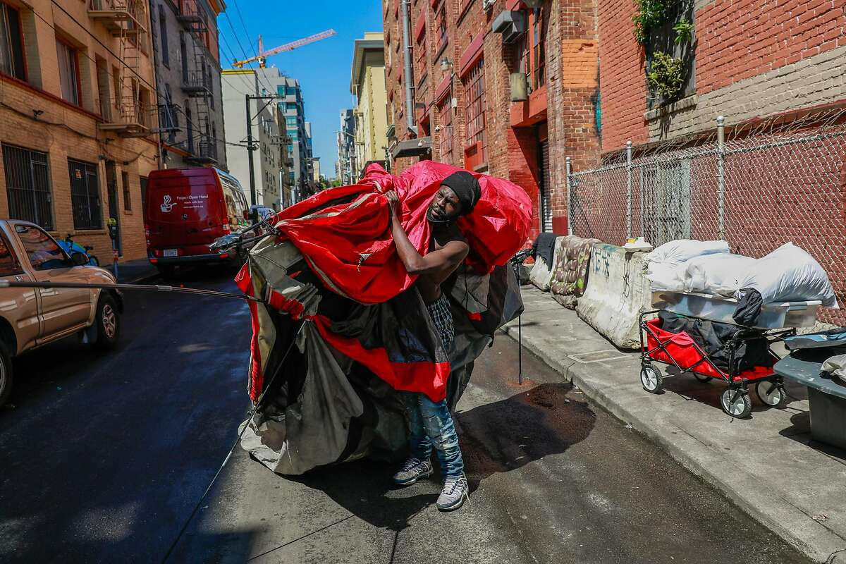 A homeless man carries his belongings after street cleaners arrived on Willow Street in the Tenderloin in May 2020.