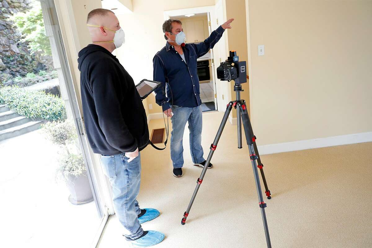 Realtor David Grega (right) directs photographer Tom Sparks as Sparks creates a 3-D interactive tour of a rental property in Sausalito, Calif., on Thursday, April 16, 2020.