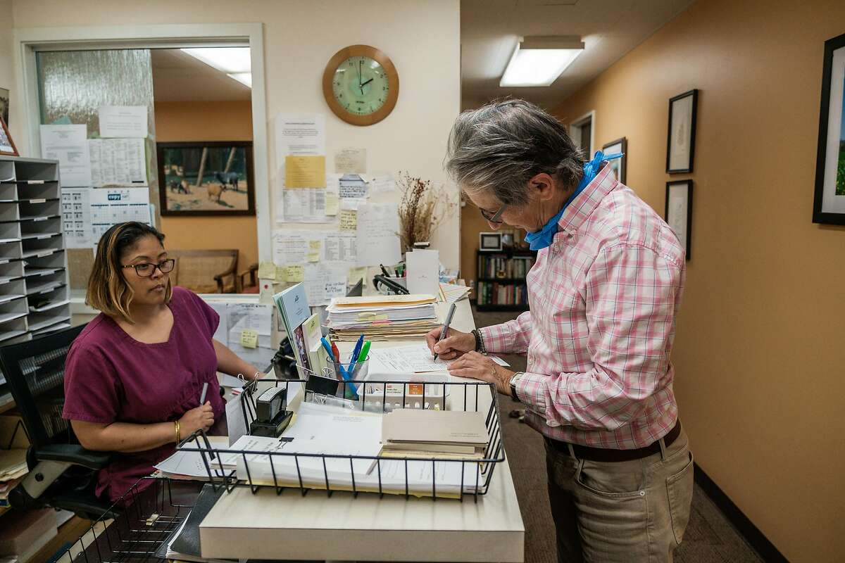 Dr. Lisa Capaldini and medical assistant Melissa Edwards go over some paper work in Dr. Capaldini�s office in San Francisco, Calif. on Friday, May 15, 2020.