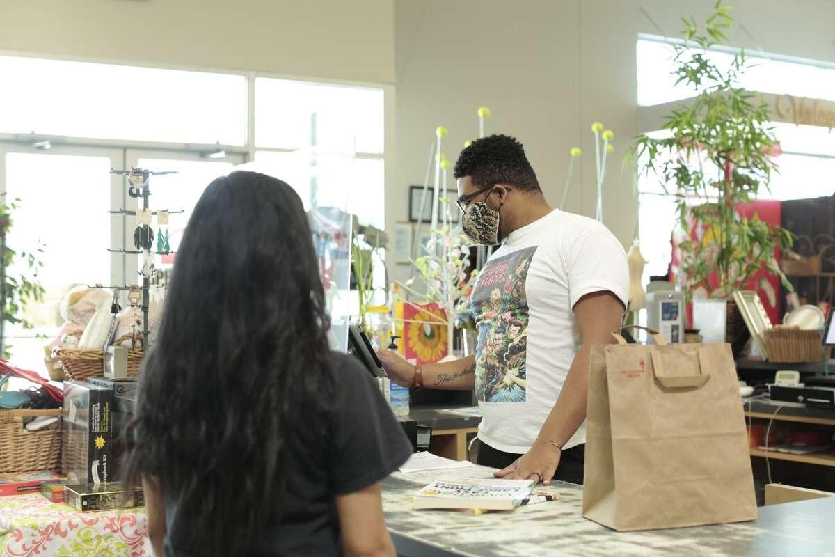 Resale Associate John Perkins helps a customer during MAM Resale reopening.