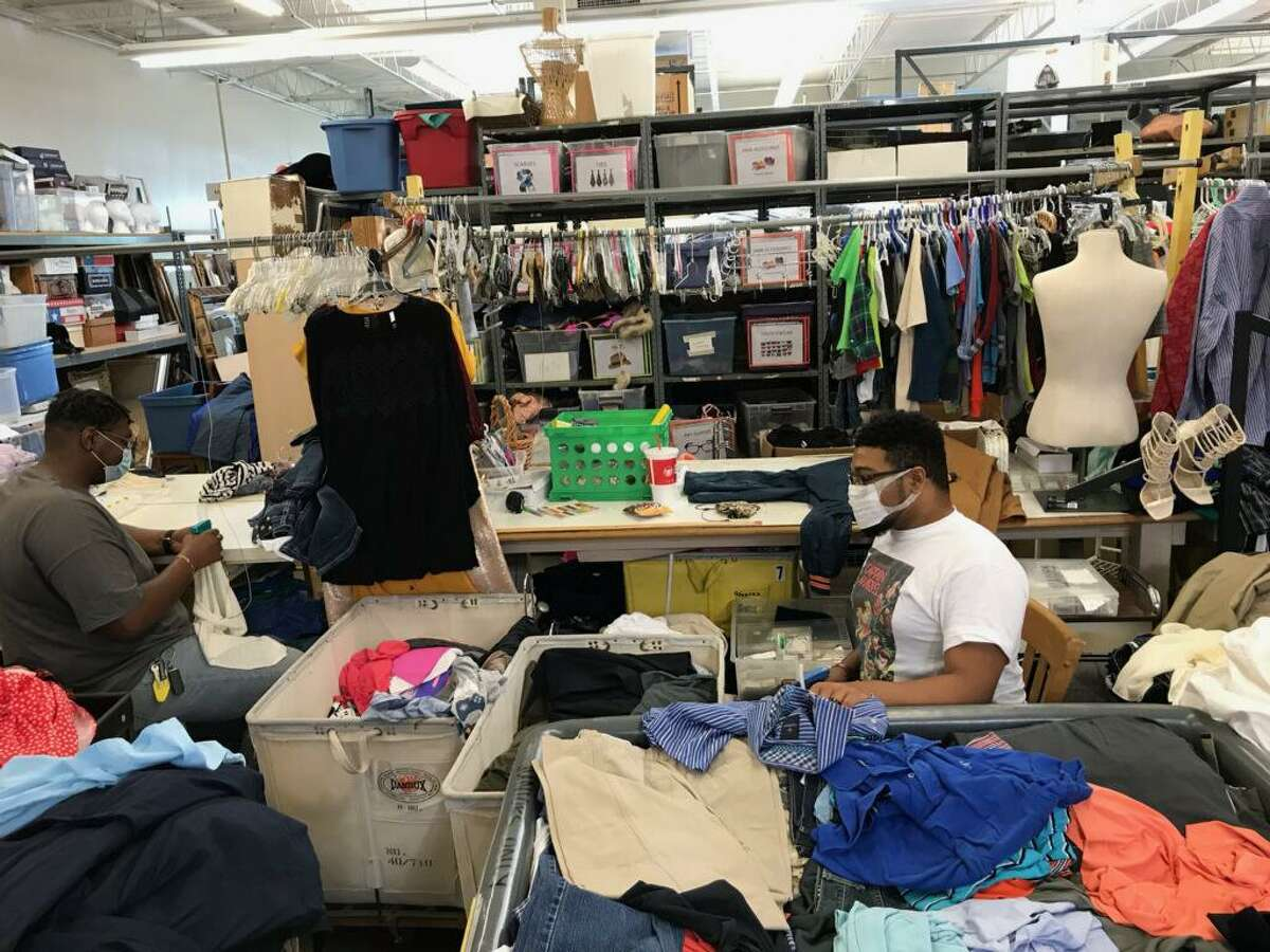 Resale associate John Perkins sorts and selects clothing for his weekly Facebook Live sales.