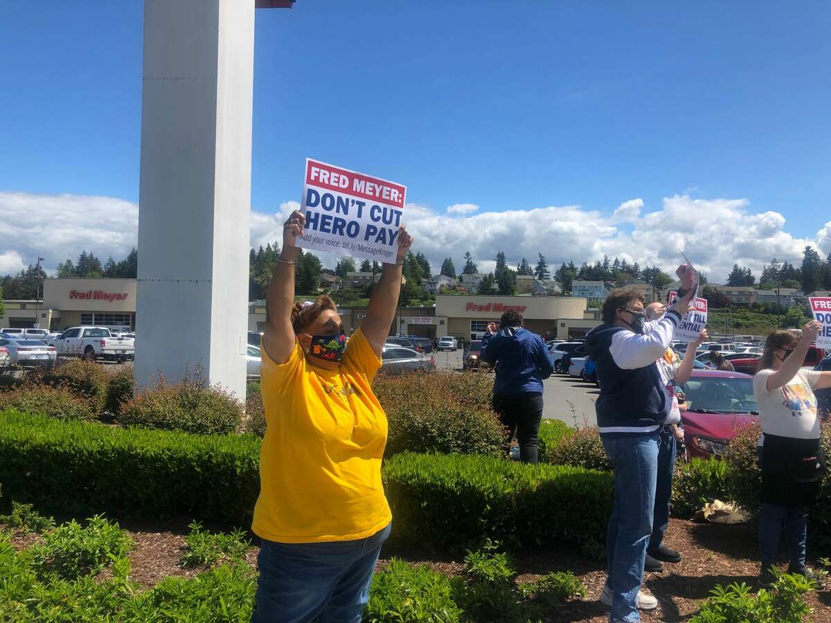 Grocery store workers protest in front of the Fred Meyer in Burien after the company announced plans to cut