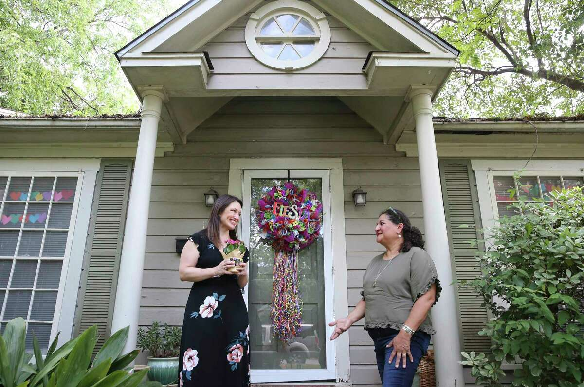 Debbie Alcoser, right, hands a bouquet of flowers and a gift card to Alisha Coyle, who gave away a washer and dryer during a contest on the Just Give It Away! 09 Facebook group. Alcoser created the group several years ago as a forum for people to give away unwanted items in Alamo Heights and nearby suburbs.