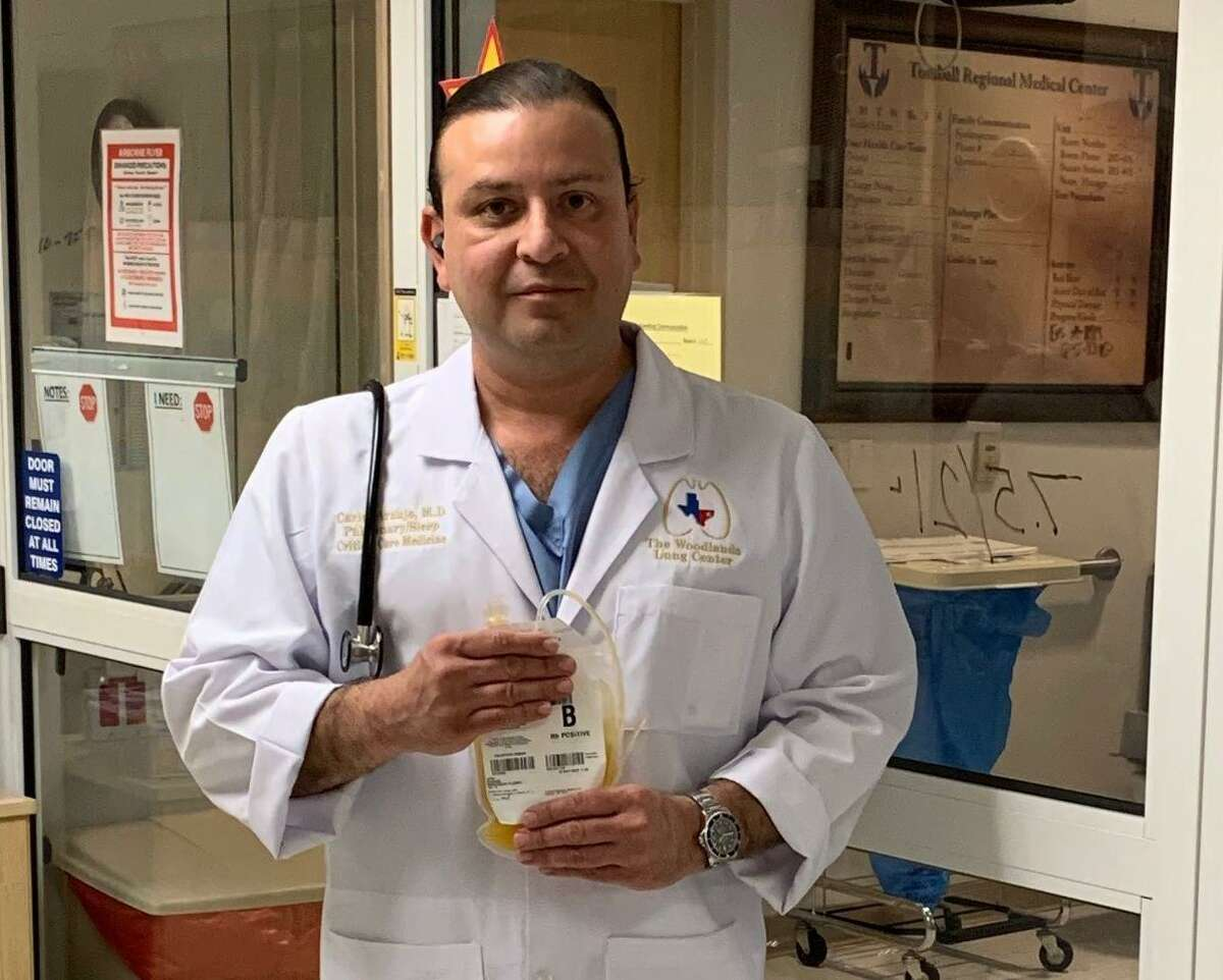 Carlos Araujo-Preza, MD, critical care medical director at HCA Houston Healthcare Tomball stands with a bag of convalescent plasma to treat a seriously ill COVID-19 patient.