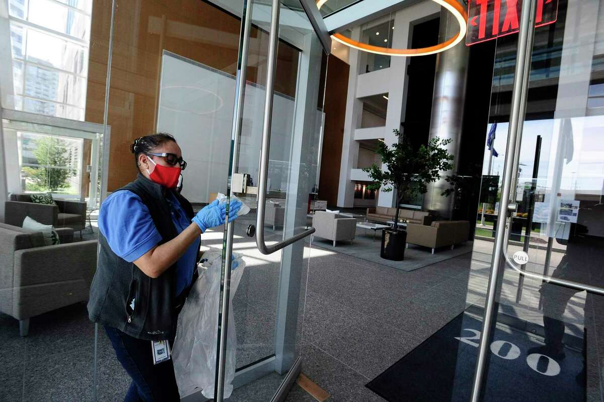 Maria Lima, a custodial porter at the Building and Land Technology-owned office building at 200 Elm St., in downtown Stamford, Conn., wiped down surfaces on May 15, 2020 in the front lobby ahead of the building's re-opening five days later.