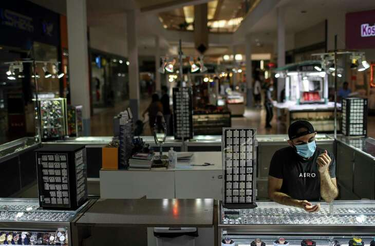 Mohammad Irfan waits for customers Friday, May 1, 2020, at PlazAmericas mall in Houston. Retailers are trying to figure out how to safely open after Governor Greg Abbott allowed some Texas business to reopen May 1 at reduced capacity, despite the COVID-19 pandemic.