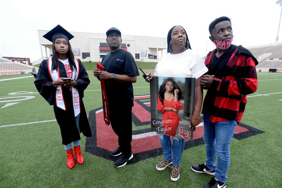 "From left, Taylor Colbert, who graduated with a B.S in nursing, her father Quinthen Colbert, mother Amber Branch and brother William Lee watch as fellow graduates are shown as Lamar University Spring 2020 graduates's names and photos are displayed on the jumbo screen at Provost Umphrey Stadium during a virtual commencement ceremony Friday. Branch says, although the ceremony was not what anyone expected, ""For what it is, it's still a blessing."" Taylor, for whom the virus altered the finale of her collegiate experience, may soon find herself ensconced in the pandemic in a whole new way. She will be working in the E.R. at Christus - ST. Elizabeth. Colbert says it is a crazy time to be starting a career in the health field. ""It's more scary for Mama,"" Branch said. Graduates and their families were invited to take photos as their name and picture were displayed, although early morning rains made for a sparse attendance at the day-long event start. Photo taken Friday, May 15, 2020 Kim Brent/The Enterprise Photo: Kim Brent/The Enterprise"