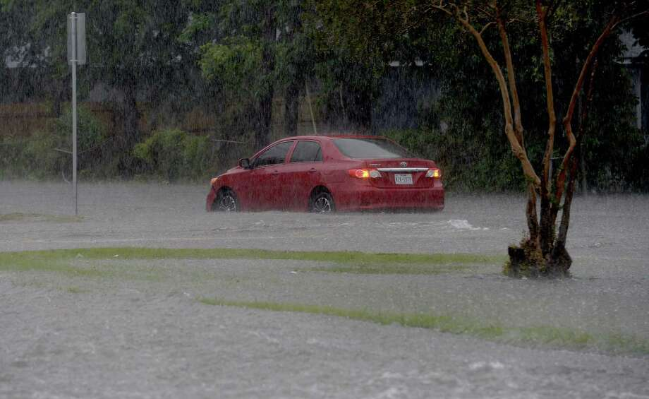 Vehicles make their way through a section of Phelan Boulevard, which quickly flooded, stalling out smaller vehicles caught amid the quickly rising water following heavy storms late Thursday afternoon. Photo taken Thursday, May 14, 2020 Kim Brent/The Enterprise Photo: Kim Brent / The Enterprise / BEN