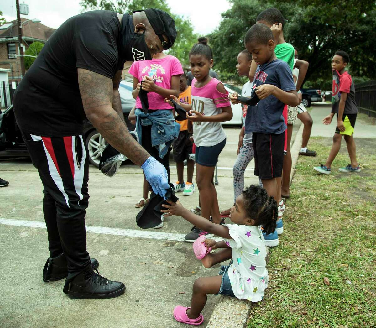"""Rap artist Trae The Truth hands out masks to a group of kids in the Third Ward on Wednesday, May 13, 2020 in Houston. The rapper spent the day handing out 10,000 masks to people in neighborhoods all around the city. """"I am trying to get masks to people who wouldn't normally be able to get one,"""" he said."""