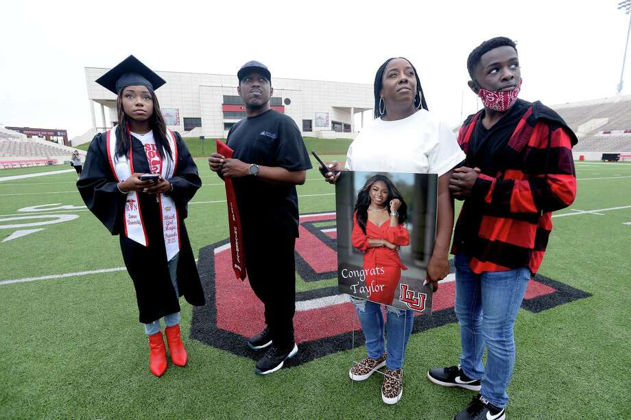 """From left, Taylor Colbert, who graduated with a B.S in nursing, her father Quinthen Colbert, mother Amber Branch and brother William Lee watch as fellow graduates are shown as Lamar University Spring 2020 graduates's names and photos are displayed on the jumbo screen at Provost Umphrey Stadium during a virtual commencement ceremony Friday.  Branch says, although the ceremony was not what anyone expected, """"For what it is, it's still a blessing."""" Taylor, for whom the virus altered the finale of her collegiate experience, may soon find herself ensconced in the pandemic in a whole new way. She will be working in the E.R. at Christus - ST. Elizabeth. Colbert says it is a crazy time to be starting a career in the health field. """"It's more scary for Mama,"""" Branch said. Graduates and their families were invited to take photos as their name and picture were displayed, although early morning rains made for a sparse attendance at the day-long event start. Photo taken Friday, May 15, 2020 Kim Brent/The Enterprise Photo: Kim Brent / The Enterprise / BEN"""