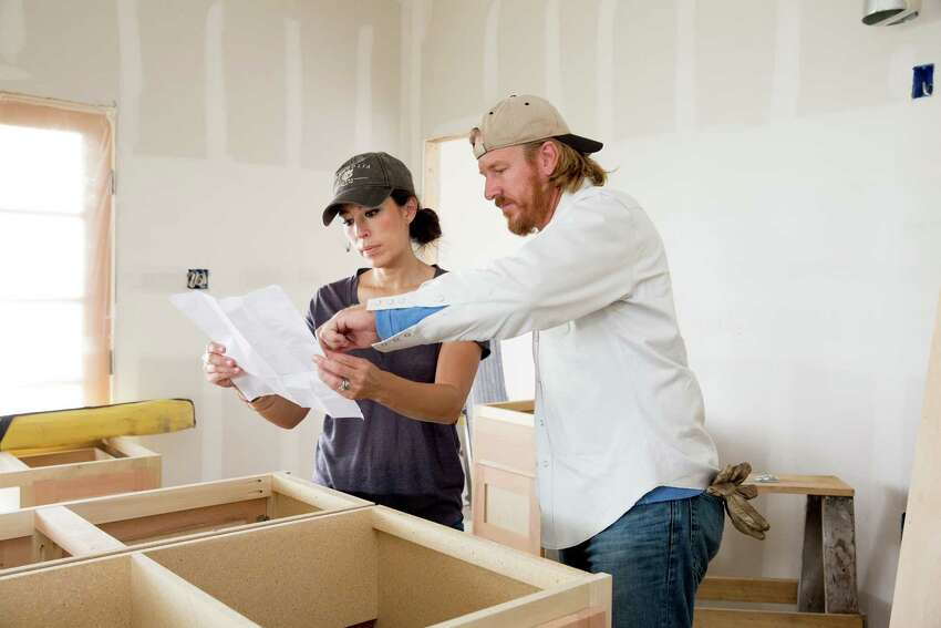 In an undated image provided by Magnolia, Chip and Joanna Gaines discuss cabinets while working on a home. The Gainesa€™s home design work seems to divide along traditional gender lines, but Joanna is the driving force behind the brand. (Magnolia via The New York Times) -- NO SALES; FOR EDITORIAL USE ONLY WITH NYT STORY HOME POWER COUPLE BY JULIA MOSKIN FOR MAY 4, 2020. ALL OTHER USE PROHIBITED. --