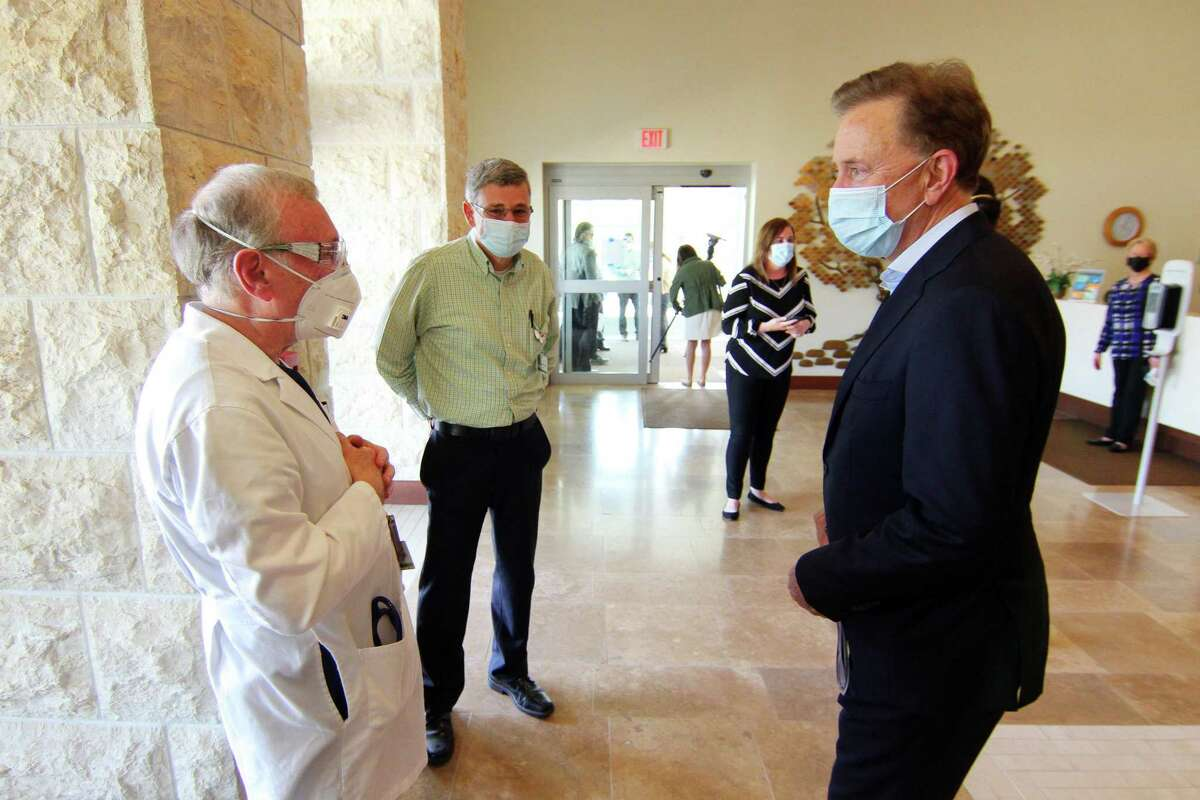 Gov. Ned Lamont, right, chats with Dr. Kenneth Fine during a visit to The Jewish Home senior services facility on Park Ave in Bridgeport, Conn., on Friday May 15, 2020.