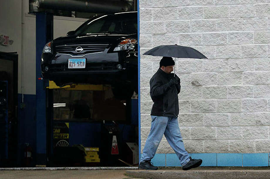 A man holds an umbrella while he walks in front of an auto repair shop in Wheeling. Nearly 3 million laid-off workers applied for U.S unemployment benefits last week as the COVID-19 pandemic forced more companies to slash jobs, even though most states have begun to let some businesses reopen. Photo: Nam Y. Huh | AP