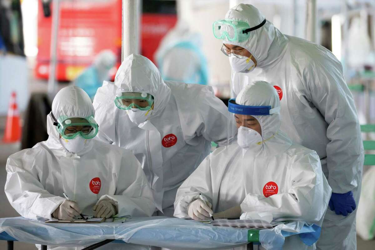 Medical staff in protective gear work at a coronavirus testing station at Incheon International Airport in Incheon, South Korea, on April 1, 2020.