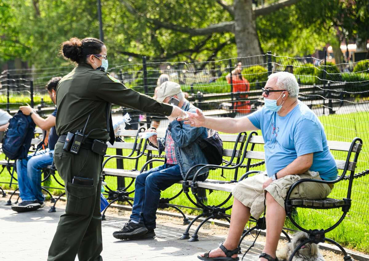 New York City Parks Enforcement Patrol officer gives face masks to people in Washington Square Park during the coronavirus pandemic on May 15, 2020 in New York City. COVID-19 has spread to most countries around the world, claiming over 308,000 lives with over 4.6 million infections reported.