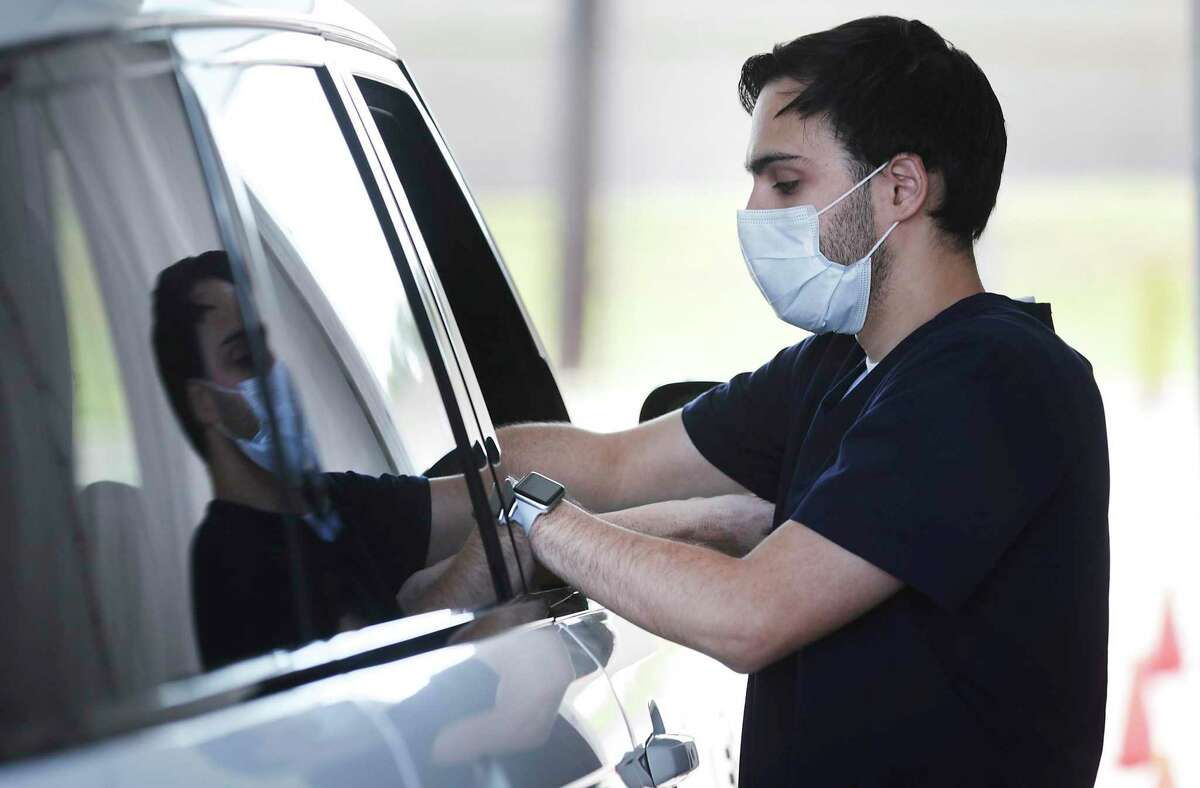 Jacob Gaier, a medical assistant with Remedy, an Austin-based telemedicine company that opened a drive-up site in San Antonio, takes a blood sample from a customer who requested the antibody test for coronavirus, on Thursday, May 14, 2020.