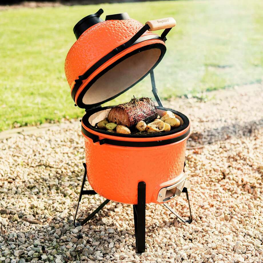This photo provided by Riverbend Home shows the BergHOFF Small Ceramic BBQ Grill. This wood or charcoal grill is a good smaller size for urban patios, and can be used for searing, roasting, grilling or low-temperature smoking. The ceramic exterior is another grill offered in on-trend orange, as well as dark grey. (BergHOFF/Riverbend Home via AP) Photo: Associated Press / BergHOFF/Riverbend Home