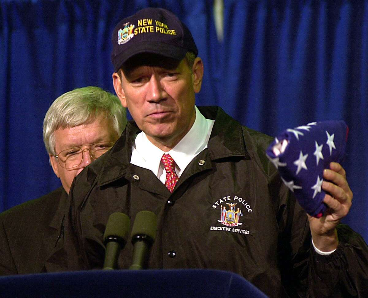 New York Gov. George Pataki holds an American flag, which earlier flew over the capitol, that was given to him by House Speaker Dennis Hastert, left, Oct. 1, 2001, in New York. More than 100 congressional members toured the site of the World Trade Center.