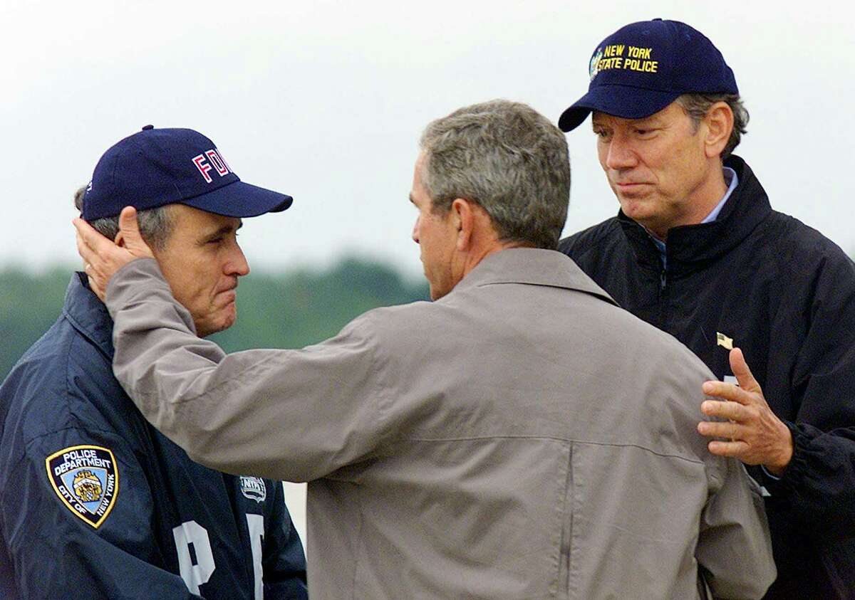 President Bush greets New York City Mayor Rudolph Giuliani, left, and New York Gov. George Pataki, right, at McGuire Air Force Base, N.J., Friday, Sept. 14, 2001. Bush toured the disaster site of the World Trade Center in New York later on foot after getting a helicopter view of the devastation.