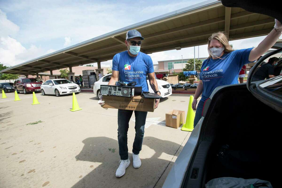 Roy Reyes, community support specialist with Communities In Schools, and Lisa Descant load a computer into the back of a vehicle while helping distribute desktop computers to the students at Ridgecrest Elementary School on Friday, May 15, 2020 in Houston. Communities In Schools of Houston distributed 275 computers to help the Ridgecrest students with remote learning amid the coronavirus pandemic and school closings. CIS is teaming up with Comp-U-Dopt to distribute 5,000 computers across the city needed for virtual school work.