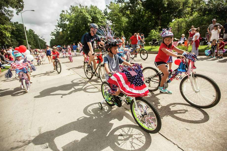 Kids ride their bikes decked out with patriotic decorations during the Kingwood 4th of July Parade on July 4, 2015, in Kingwood. Photo: ANDREW BUCKLEY / Internal