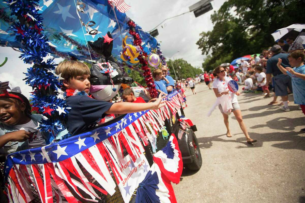 Kids from Good Shepherd Episcopal School throw candy to the crowd during the Kingwood 4th of July Parade on July 4, 2015, in Kingwood.
