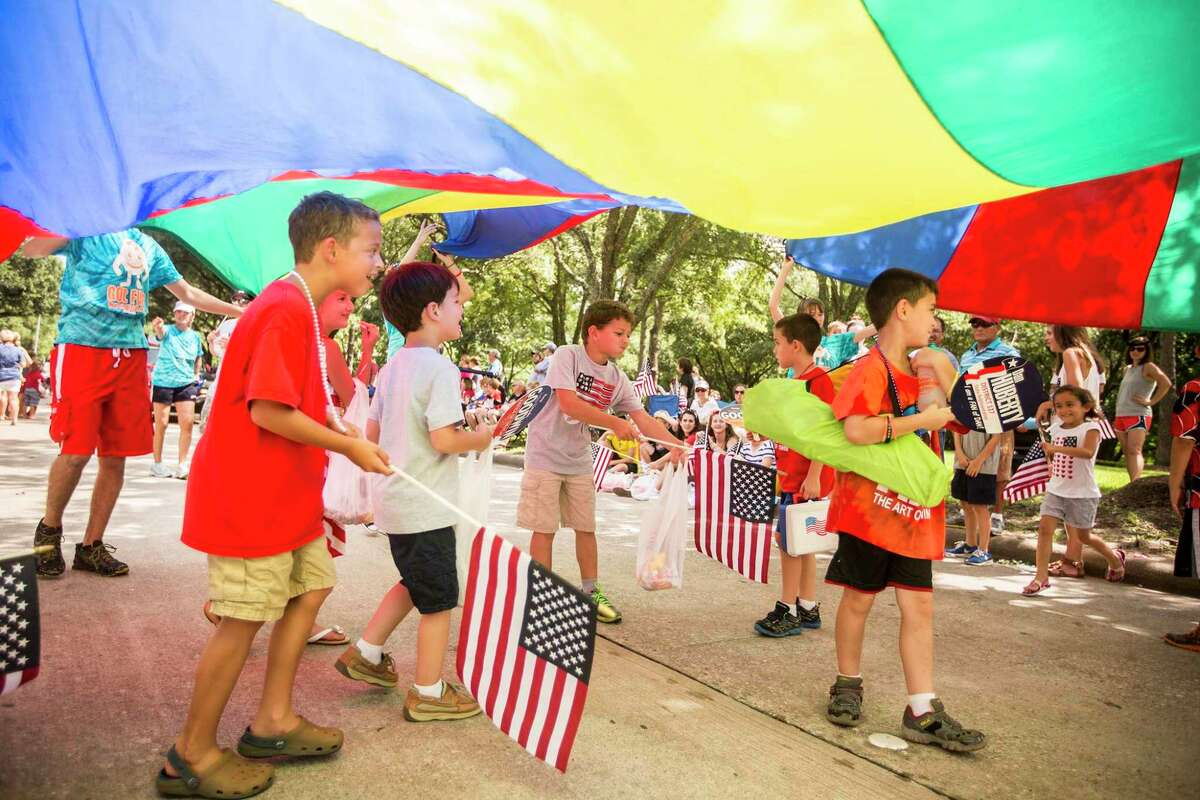 Kids play under a rainbow tent on the parade route during the Kingwood 4th of July Parade on July 4, 2015, in Kingwood.