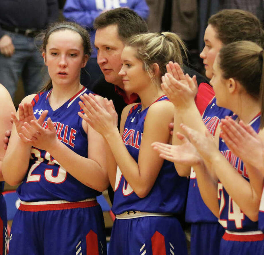 Carlinville coach Darrin DeNeve advises senior girls basketball players Sarah DeNeve (left) and Corin Stewart before they accept the championship plaque after winning the Carlinville Class 2A Regional on Feb. 14. Photo: Greg Shashack / The Telegraph