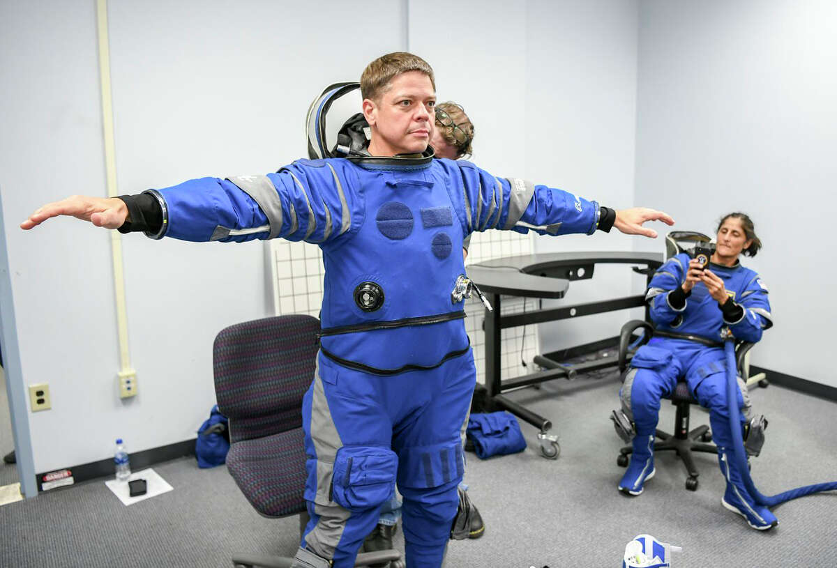 Bob Behnken puts on his spacesuit at Kennedy Space Center in Cape Canaveral, Florida. On May 27, 2020, he and fellow astronaut Doug Hurley are set to be lifted to the International Space Station by a booster and spacecraft owned and operated by SpaceX.