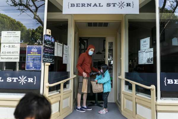 SAN FRANCISCO, CALIFORNIA - MAY 8, 2020: To avoid tech middlemen delivery fees and support local businesses, a growing number of San Francisco Bay Area residents are supporting local small businesses, like Bernal Star where neighborhood customers, Ryan Jang and Madeleine Jang, 7, pick up dinner as well as free deliveries of farmers veggie, beverage, and fresh fish boxes, in Bernal Heights neighborhood of San Francisco, California Friday May 8, 2020. (Photo by Melina Mara/The Washington Post via Getty Images)