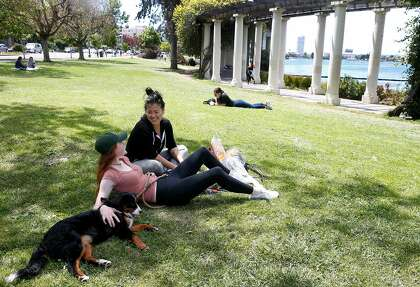 Sammy Consani and Nutella (left) sits with Hannah Suh at Lake Merritt in Oakland this month. Oakland city officials are strongly discouraging gatherings at the lake and at parks and are reminding people to maintain social distancing during the coronavirus shelter in place orders.