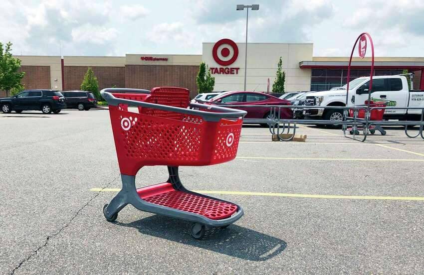 FILE - In this June 3, 2019, file photo a shopping cart sits in the parking lot of a Target store in Marlborough, Mass. Plenty of retailers like Target and Walmart allow shoppers to drop off online returns at their stores. But now, a growing number of retailers are accepting rivalsa€™ returns. (AP Photo/Bill Sikes, File)