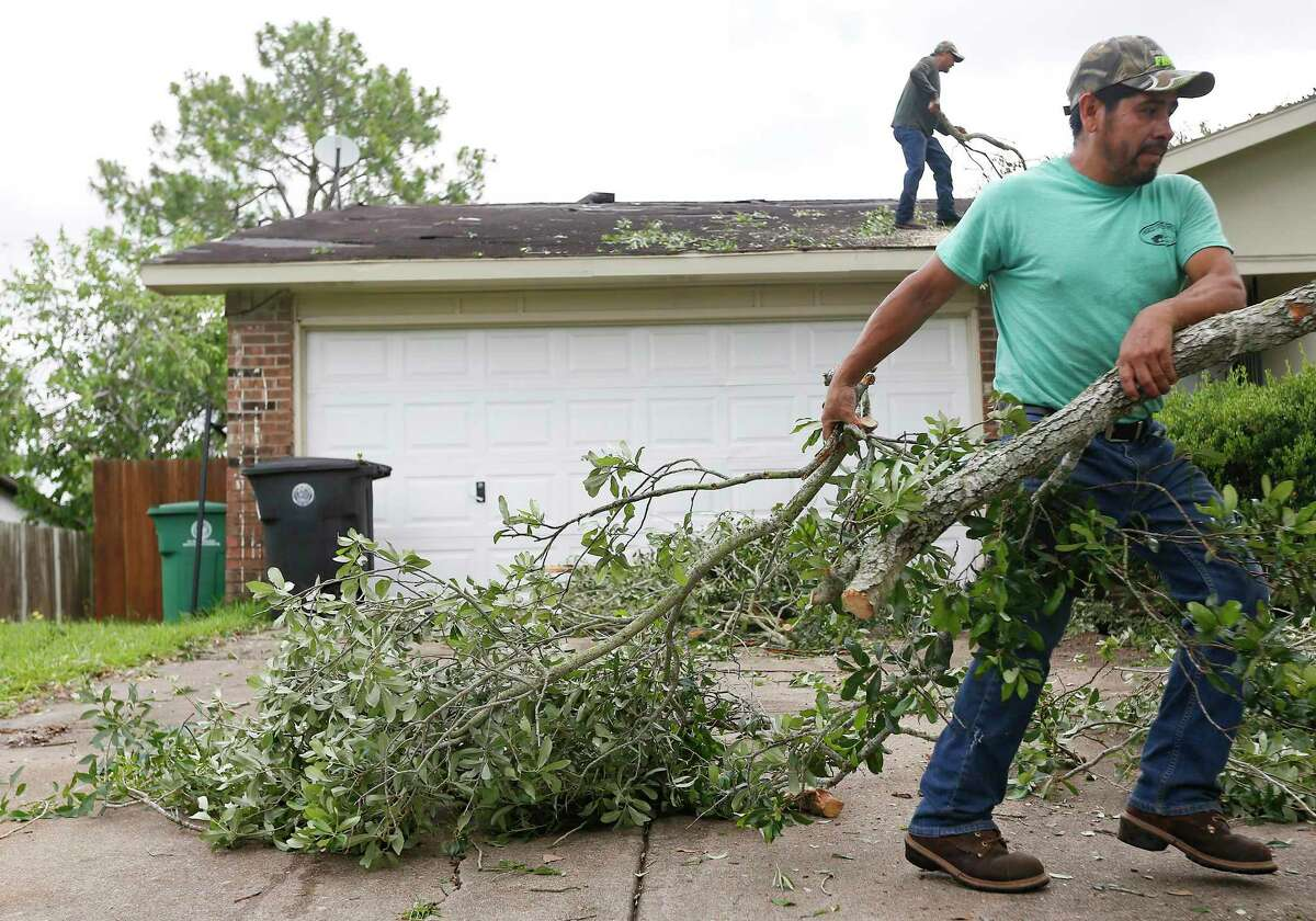 Tree service contractors remove branches from the roof of a home on Ridgecreek Drive in Houston on Saturday, May 16, 2020. The damage was from a storm that blew through Saturday morning.