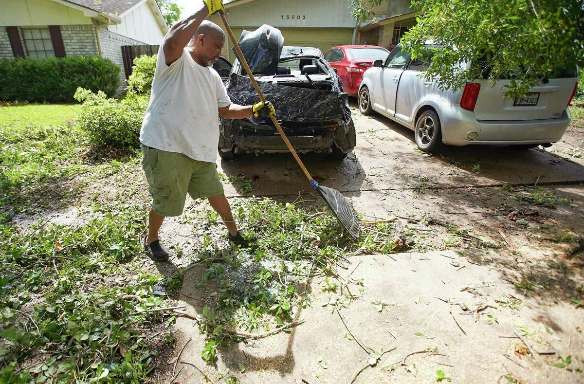Kenny Willett racks branches off his driveway as he makes way for a tow truck in Houston on Saturday, May 16, 2020. A storm that blew through early Saturday morning caused large branches to fall on all three vehicles in Willett's driveway.