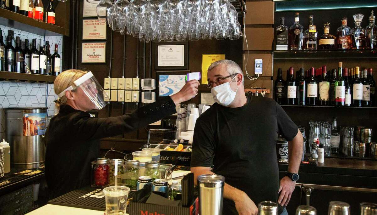 1920 Tavern Owner Jenna Aronowitz takes the temperature of bartender Shane Goode before the Roswell restaurant opens for sit down meals in Brookhaven, Ga., on April 27.