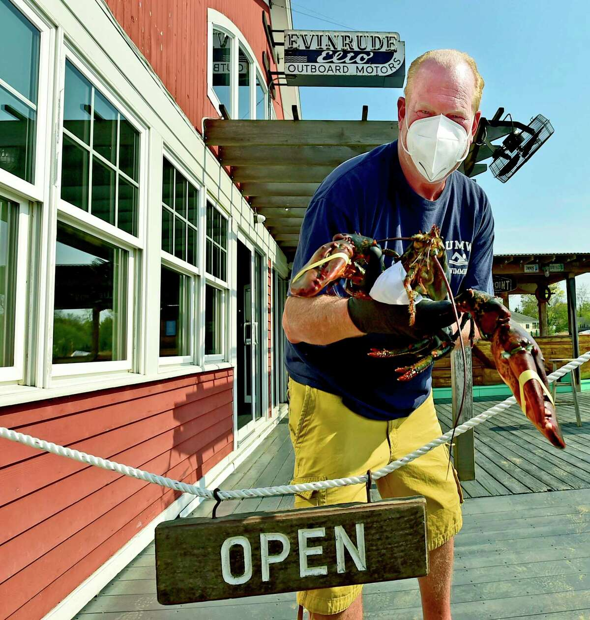 Branford, Connecticut - Friday, May 15, 2020: Christopher Conlin owner of Lenny's Indian Head Inn, a classic New England seafood restaurant holds a 9-pound lobster at the new entrance on the back deck and patio to maintain an adequate entrance and egress to control social-distancing flow as people get their food as Connecticut restaurants prepare for a staged May 20th opening due to the Coronavirus / Covid-19 pandemic.