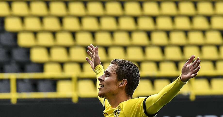 Dortmund's Thorgan Hazard plays to the empty tribune after scoring his side's third goal Saturday. Photo: Martin Meissner / Associated Press