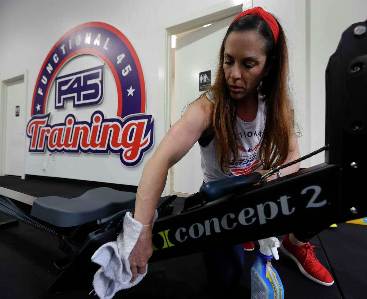 Co-owner Jodi Tompkins sanitizes equipment at F45 Training on Saturday in Montgomery. Gyms are able to reopen Monday at 25 percent capacity as part of Texas' phased reopening.