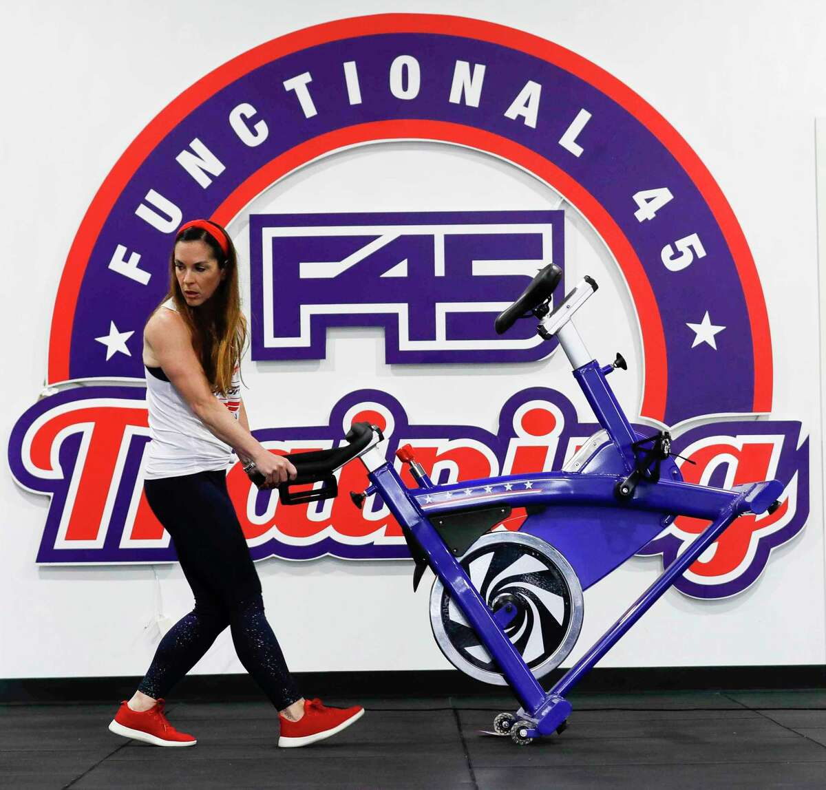 Co-owner Jodi Tompkins moves equipment so the floor can be vacuumed and equipment can be sanitized at F45 Training, Saturday, May 16, 2020, in Montgomery. Gyms are able to reopen Monday at 25 percent capacity as part of Gov. Greg Abbott's phased reopening of the Texas economy.